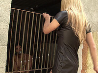 Shemale domme humiliates her caged slave