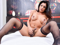 Hot Latina babe Janaina is looking good with her long black hair, her plump lips, her big perky tits and her thick cock. She is alone on bed and doing a sizzling hot solo performance for us where we witness her gorgeous body in all its glory.