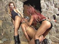 Two ts dommes working over a slave in the dungeon