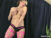 Transexual Delia poses in fencenet thigh-highs.