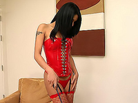 Impatient shemale in red stuffs a dildo up her ass