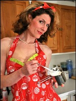 Delia frosts her cupcakes in heels, stockings, and pin-up apron.